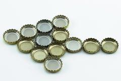 Casquillos decorativos de la cerveza en el fondo blanco Cubierta del metal de las botellas de cristal imagenes de archivo