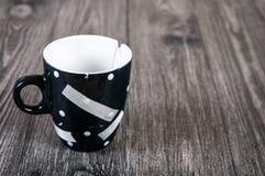 Cassé et collé avec une tasse d'emplâtre adhésif Le concept de la destruction des relations, l'espace libre pour le texte Image stock