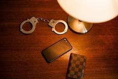 Cassa delle manette, dello smartphone e del telefono sulla tavola fotografia stock