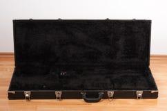 Cassa di cuoio nera per la chitarra elettrica sul pavimento in salone fotografia stock