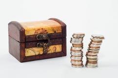 Cassa e mucchi di legno delle monete Fotografie Stock