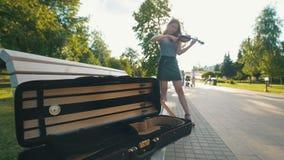Cassa per il violino che si trova sul banco davanti alla femmina che gioca le fiddle al tramonto stock footage