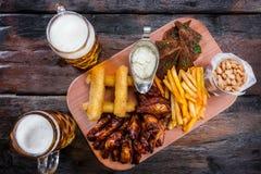 Casse-croûte assortis de bière avec des tasses de bière photo libre de droits