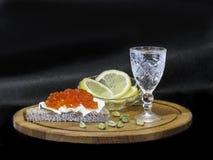 Casse-croûte avec du pain noir, le caviar rouge et le citron images libres de droits