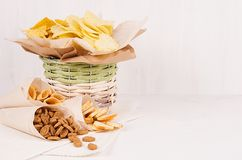 Casse-croûte colorés d'or - nachos, maïs éclaté, croûtons, pommes chips dans le panier rustique et cône de papier de métier sur l photo libre de droits
