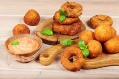 Casse-croûte délicieux : boules de fromage et anneaux d'oignon avec de la sauce Image stock