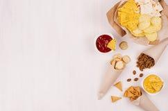 Casse-croûte d'été - le nacho, les croûtons, les frites, la tortilla dans le cône de papier de métier et le Salsa sauce sur le fo photographie stock