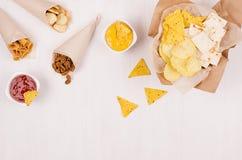 Casse-croûte d'été - le nacho, les croûtons, les frites, la tortilla dans le cône de papier de métier et le Salsa sauce sur le fo images stock