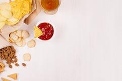 Casse-croûte d'or croustillants sur la sauce à papier de métier, à nachos de triangles, blonde à bière, rouge et jaune dans la cu photos libres de droits