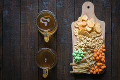 Casse-croûte dans la bière et deux tasses de bière blonde, sur une table en bois, dans une barre Arachides, arachides dans une co Photographie stock
