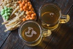 Casse-croûte dans la bière et deux tasses de bière blonde, sur une table en bois, dans une barre Arachides, arachides dans une co Images stock