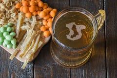 Casse-croûte dans la bière et la tasse de bière blonde, sur une table en bois, dans une barre Arachides, arachides dans une coqui Photo libre de droits