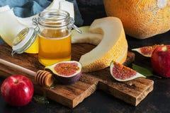 Casse-croûte de fruit de melon, de figues, de pommes rouges et de miel Foyer sélectif photos libres de droits