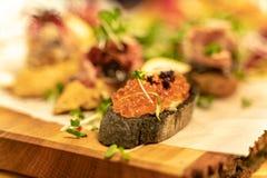 Casse-croûte de vin d'antipasti de caviar réglés avec la profondeur du foyer au-dessus du fond grunge foncé photographie stock