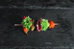 Casse-croûte espagnol, banderillas sur des brochettes le poivron avec de salami, de marinage olives, conserves au vinaigre, vert  Images libres de droits