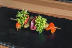 Casse-croûte espagnol, banderillas sur des brochettes le poivron avec de salami, de marinage olives, conserves au vinaigre, vert  Photographie stock
