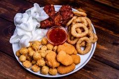 Casse-croûte frits de bière : pépites de poulet, boules et jambes, flocons de riz et anneaux d'oignon panés photographie stock