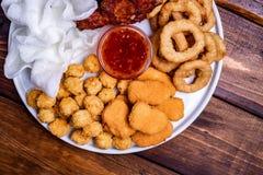 Casse-croûte frits de bière : pépites de poulet, boules et jambes, flocons de riz et anneaux d'oignon panés image stock