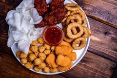 Casse-croûte frits de bière : pépites de poulet, boules et jambes, flocons de riz et anneaux d'oignon panés photo stock