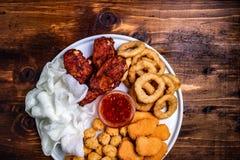 Casse-croûte frits de bière : pépites de poulet, boules et jambes, flocons de riz et anneaux d'oignon panés fond en bois sous le  images stock