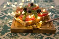Casse-croûte ou tomate saine, arugula, olives et fromage crémeux sur le pain de pain grillé Déjeuner organique photos libres de droits