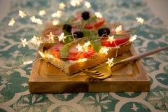 Casse-croûte ou tomate saine, arugula, olives et fromage crémeux sur le pain de pain grillé Déjeuner organique photographie stock