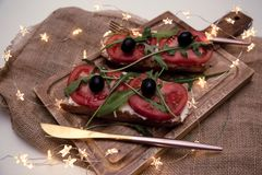 Casse-croûte ou tomate saine, arugula, olives et fromage crémeux sur le pain de pain grillé Déjeuner organique image libre de droits