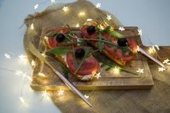 Casse-croûte ou tomate saine, arugula, olives et fromage crémeux sur le pain de pain grillé Déjeuner organique photographie stock libre de droits