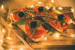 Casse-croûte ou tomate saine, arugula, olives et fromage crémeux sur le pain de pain grillé Déjeuner organique photo libre de droits