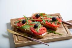 Casse-croûte ou tomate saine, arugula, olives et fromage crémeux sur le pain de pain grillé Déjeuner organique images libres de droits