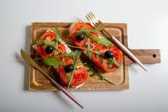 Casse-croûte ou tomate saine, arugula, olives et fromage crémeux sur le pain de pain grillé Déjeuner organique image stock
