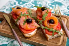 Casse-croûte sain ou poissons saumonés, arugula, olives et fromage crémeux sur le pain de pain grillé Petit déjeuner organique fr photos stock