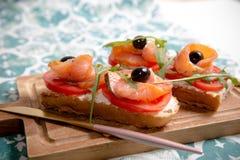 Casse-croûte sain ou poissons saumonés, arugula, olives et fromage crémeux sur le pain de pain grillé Petit déjeuner organique fr images libres de droits