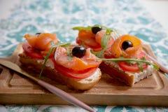 Casse-croûte sain ou poissons saumonés, arugula, olives et fromage crémeux sur le pain de pain grillé Petit déjeuner organique fr photos libres de droits