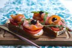 Casse-croûte sain ou poissons saumonés, arugula, olives et fromage crémeux sur le pain de pain grillé Petit déjeuner organique fr photo stock