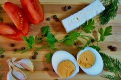 Casse-croûte savoureux avec la tomate, l'ail, le feta, l'oeuf à la coque et les verts photographie stock