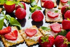 Casse-croûte : biscuits avec le fromage fondu, les fraises fraîches et les feuilles en bon état sur le fond métallique noir Images libres de droits