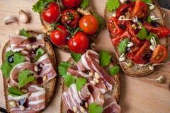 Casse-croûte de baguette de pain, de jambon de lard, de tomates, de balsamique et épices Photo stock