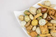 Casse-croûte mélangés riz, écrous et haricots verts secs d'un plat blanc Photographie stock libre de droits