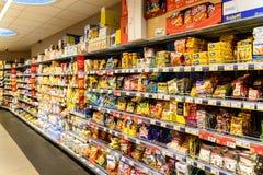 Casse-croûte malsains d'aliments de préparation rapide à vendre sur l'étagère de supermarché photos stock