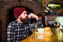 Casse-cro?te ?nerg?tique L'homme barbu de hippie brutal s'asseyent au compteur de barre Hippie d?tendant au bar Le bar détend l'e images libres de droits