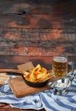 Casse-croûte savoureux crépitant des pommes chips et l'immersion et le verre épicés photographie stock libre de droits