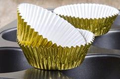 Casse della torta della tazza dorata su uno stagno di cottura Fotografia Stock Libera da Diritti