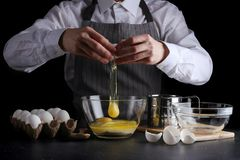 Casse l'oeuf pour la p?te tarte ou g?teau de recette faisant le concept sur le fond fonc? image stock