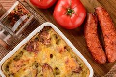 Casserole με τις πατάτες, τα λουκάνικα, τις ντομάτες και το τυρί Στοκ Εικόνα