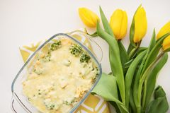Casserole with broccoli. Cheese and cream on a background of yellow tulips Stock Photos