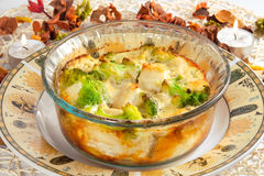 Casserole with broccoli, chicken and cheese. On plate, lighted candles on the table Stock Photo