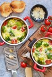 Casserole with broccoli, tomatoes and parmesan on a concrete background. View from above. Casserole with broccoli, tomatoes and parmesan on a concrete background royalty free stock image