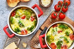 Casserole with broccoli, tomatoes and parmesan on a concrete background. View from above. Casserole with broccoli, tomatoes and parmesan on a concrete background royalty free stock photography
