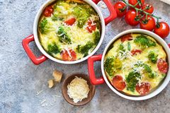 Casserole with broccoli, tomatoes and parmesan on a concrete background. View from above. Casserole with broccoli, tomatoes and parmesan on a concrete background royalty free stock images